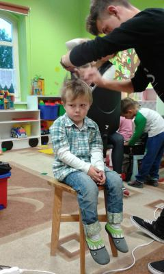 Mały uczestnik warsztatów w rękach fryzjera